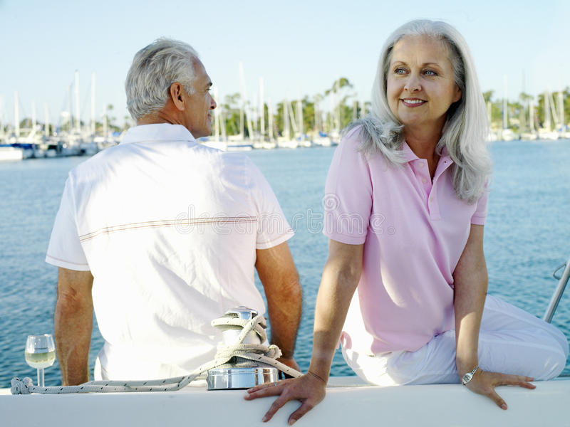 Mature couple on deck of boat, smiling stock images