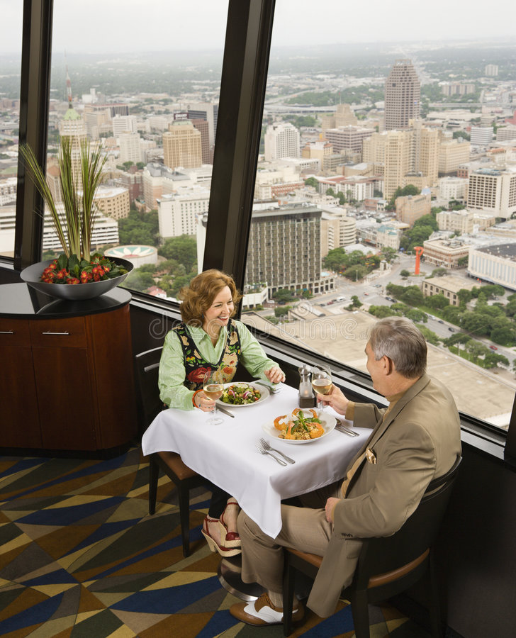 Mature couple dining. Mature couple dining in fancy restaurant by window with rooftop view of urban landscape