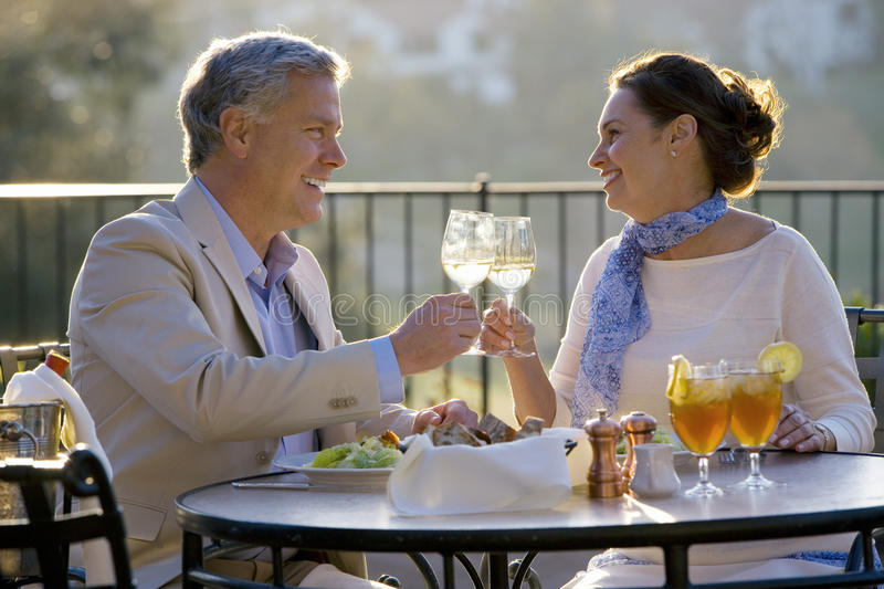 Mature couple dining at outdoor restaurant table, making celebratory toast with wine glasses, smiling, side view stock images