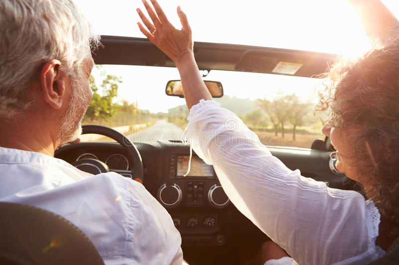 Mature Couple Driving Along Country Road In Open Top Car stock images