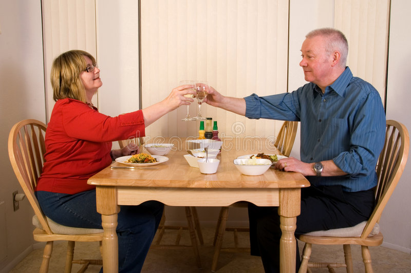 Mature couple eating dinner at home. stock images