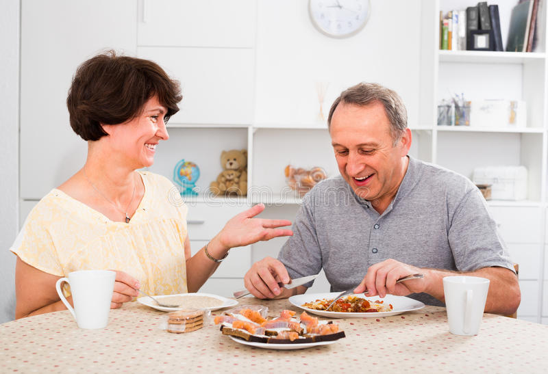 Mature couple eating lunch at home stock photos
