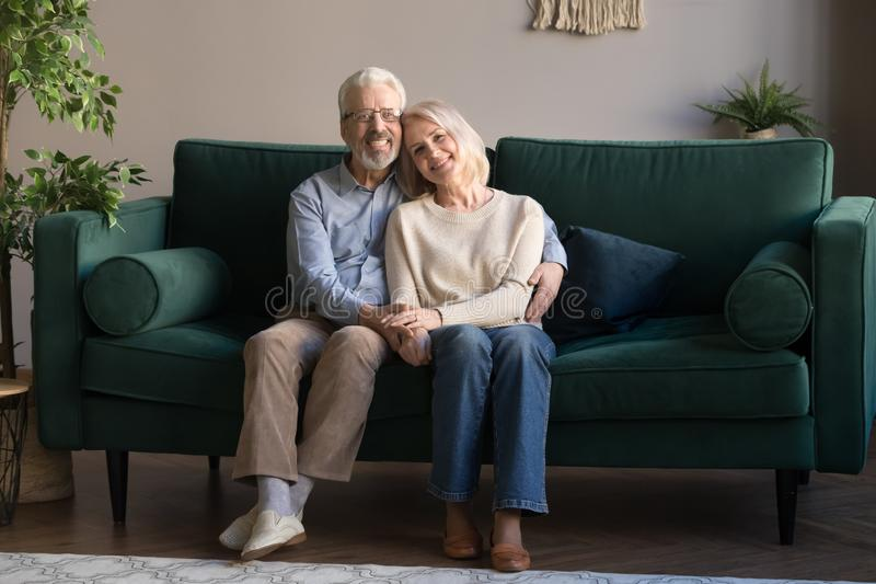 Mature couple embracing sitting on couch posing for camera. Grey haired couple in love embracing sitting on couch smiling looking at camera feels healthy stock photo