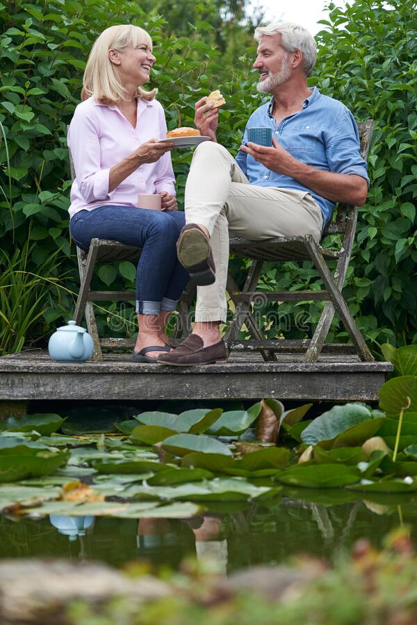 Mature Couple Enjoying Afternoon Tea And Cake Sitting On Chairs On Wooden Jetty By Lake royalty free stock photos
