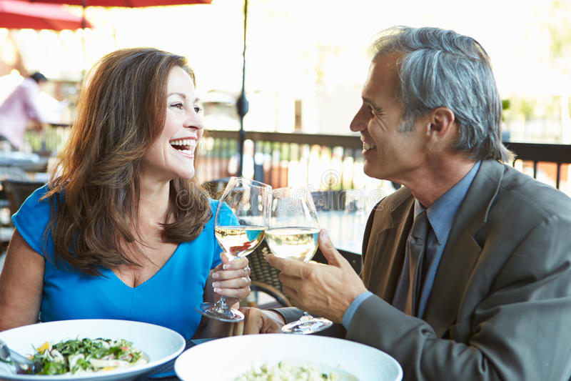 Mature Couple Enjoying Meal At Outdoor Restaurant stock image