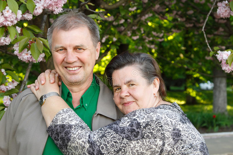 Mature couple happy hug in spring garden stock photo