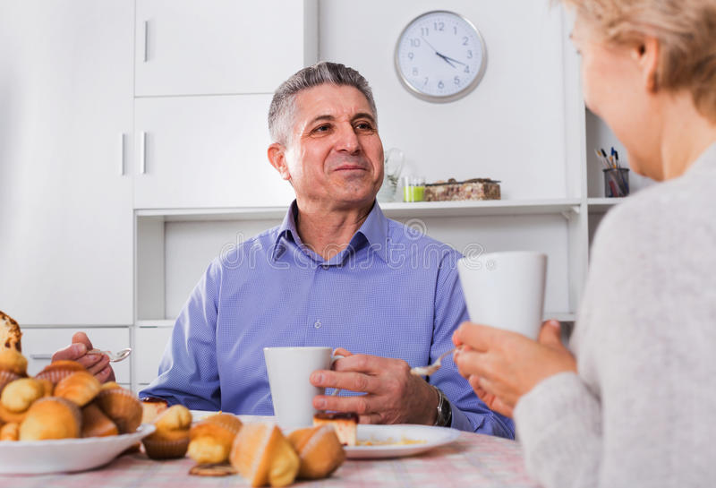 Mature couple have an afternoon snack with fresh muffins and cake royalty free stock images