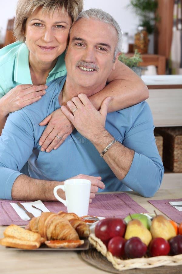 Mature couple having breakfast stock images