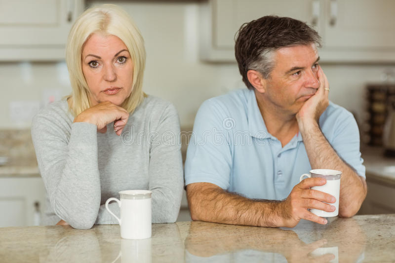 Mature couple having coffee together not talking. At home in the kitchen stock images
