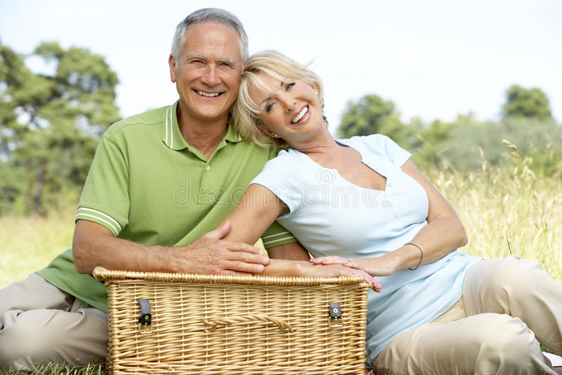 Mature couple having picnic in countryside stock image