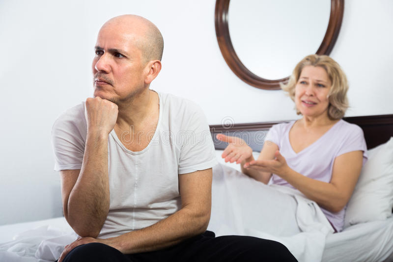Mature couple having quarrel in bedroom royalty free stock photography