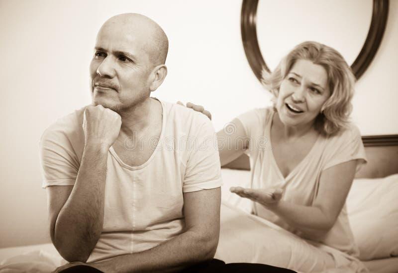 Mature couple having quarrel in bedroom stock photos