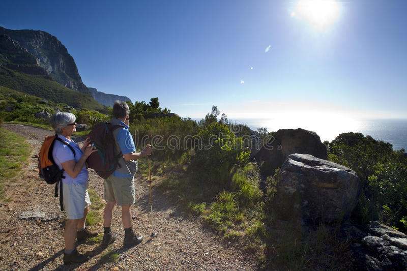 Mature couple hiking on mountain trail, looking at Atlantic Ocean horizon in bright sunlight, side view (lens flare) stock images