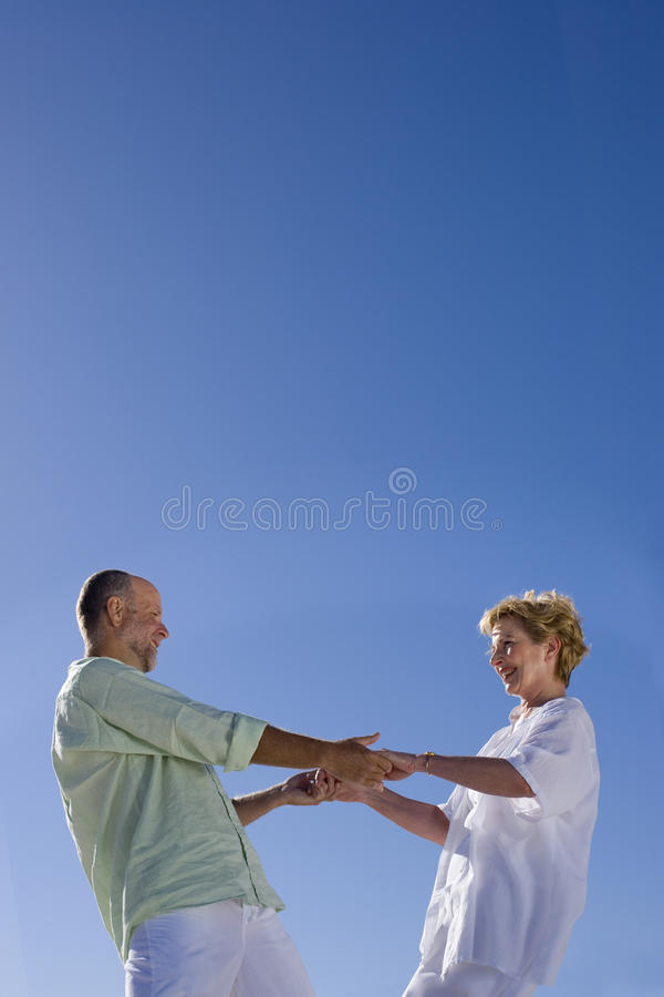 Mature couple holding hands, smiling at each other, low angle view stock photo