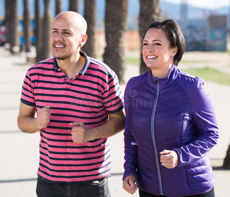 Mature couple jogging together stock photo