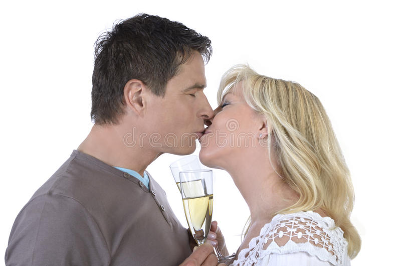Mature couple kissing with glasses of champagne