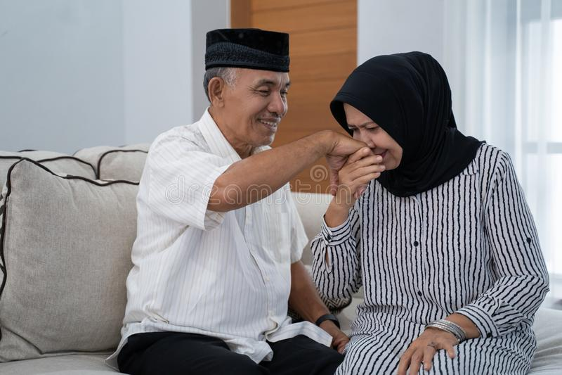 Mature couple kissing husband`s hand stock photo