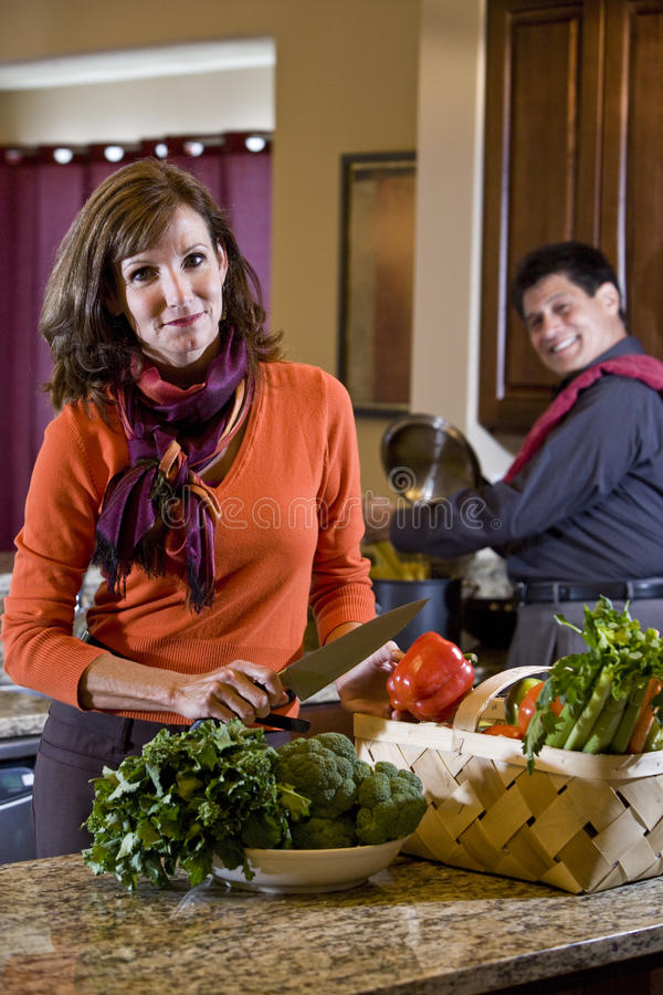 Mature couple in kitchen preparing healthy dinner stock photography