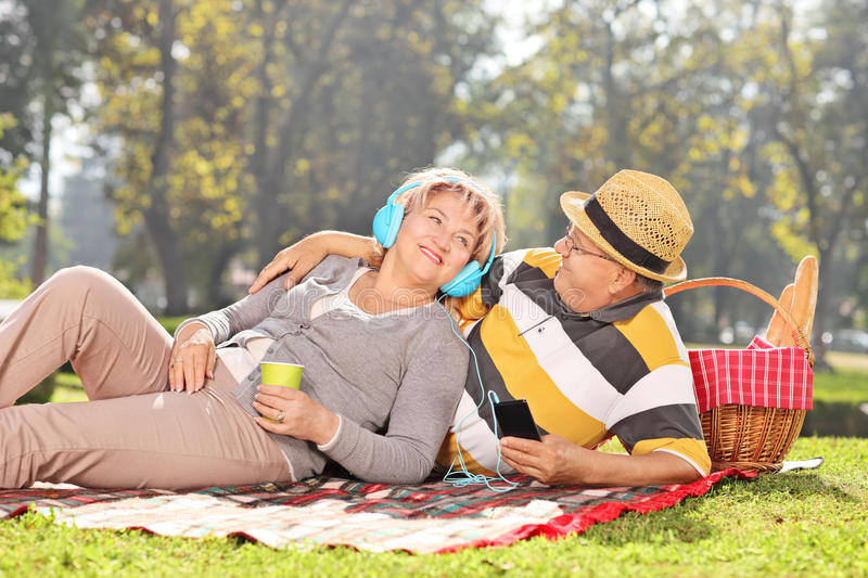 Mature couple listening music on a picnic in park royalty free stock photos