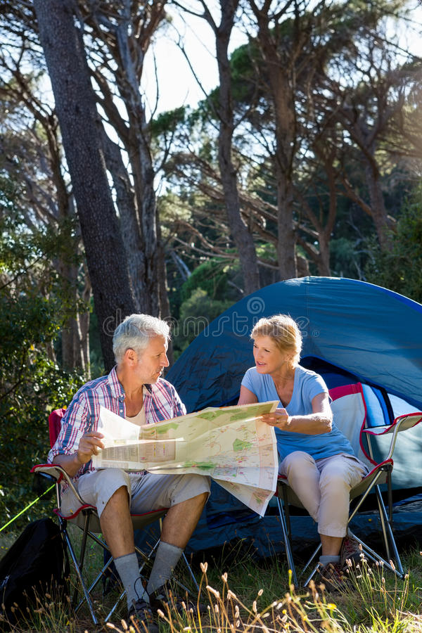 Mature couple looking map on camp site. On the wood royalty free stock photography