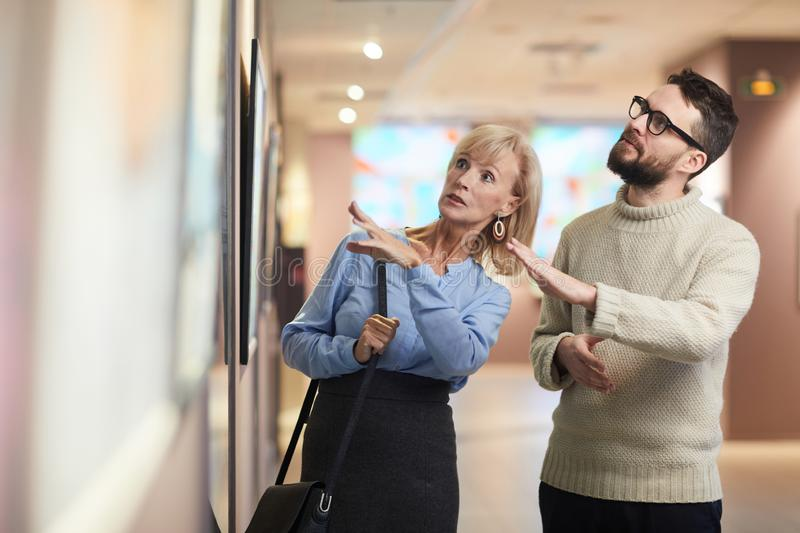 Mature Couple Looking at Paintings in Art Exhibition royalty free stock images