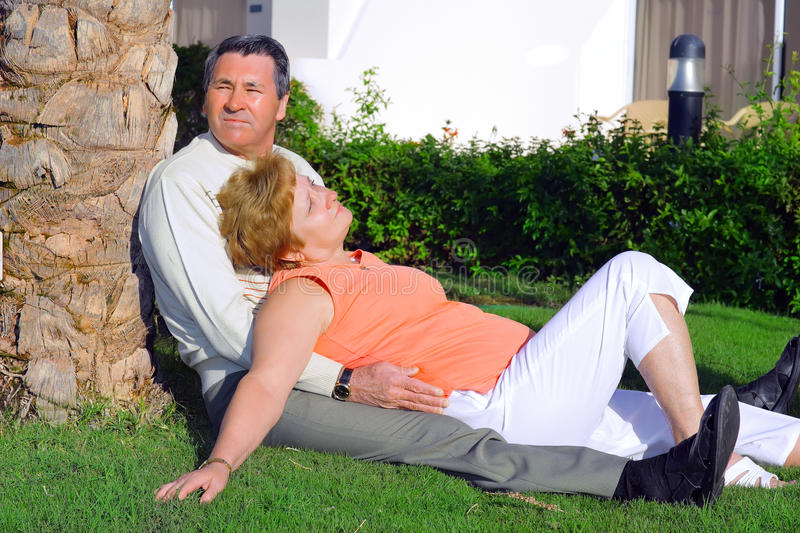 Mature couple lying in embrace near palm-tree. stock photo