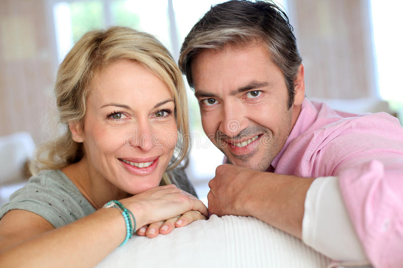 Mature couple lying on sofa royalty free stock photography