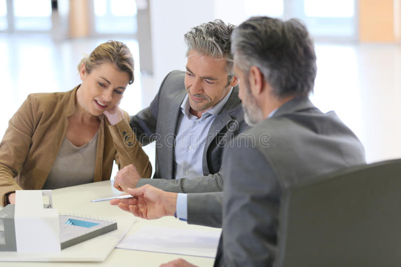 Mature couple meeting architect for construction stock photography
