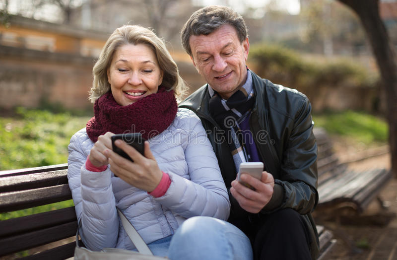 Mature couple with mobile phones on bench stock image