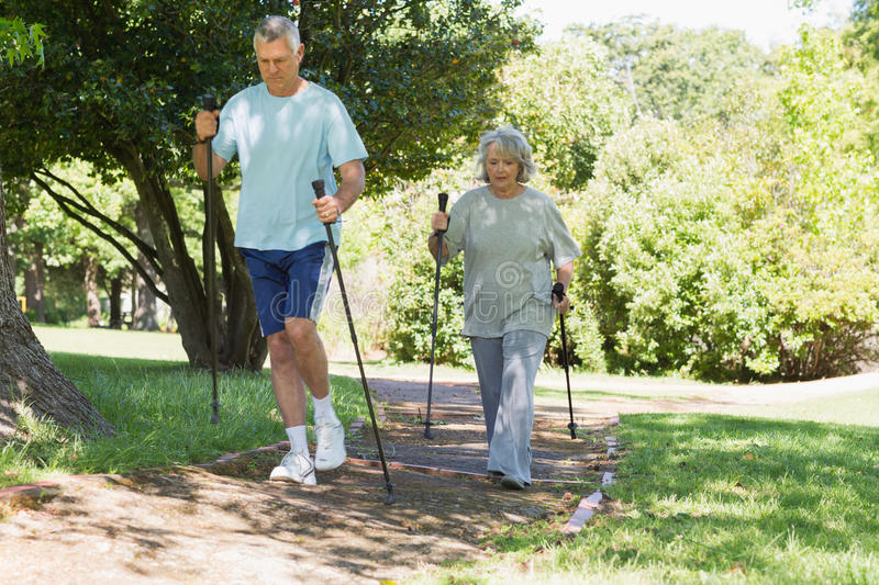 Mature couple Nordic walking at park royalty free stock photography