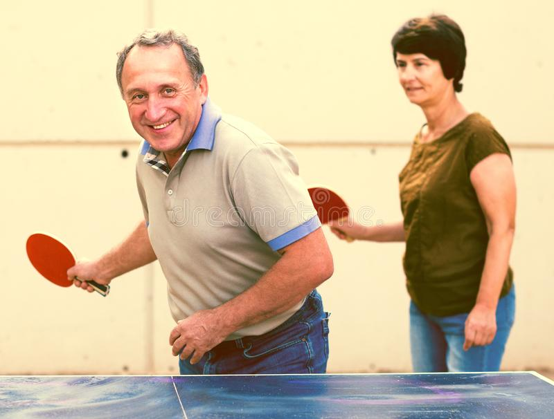Mature couple playing ping pong. Outdoors stock images