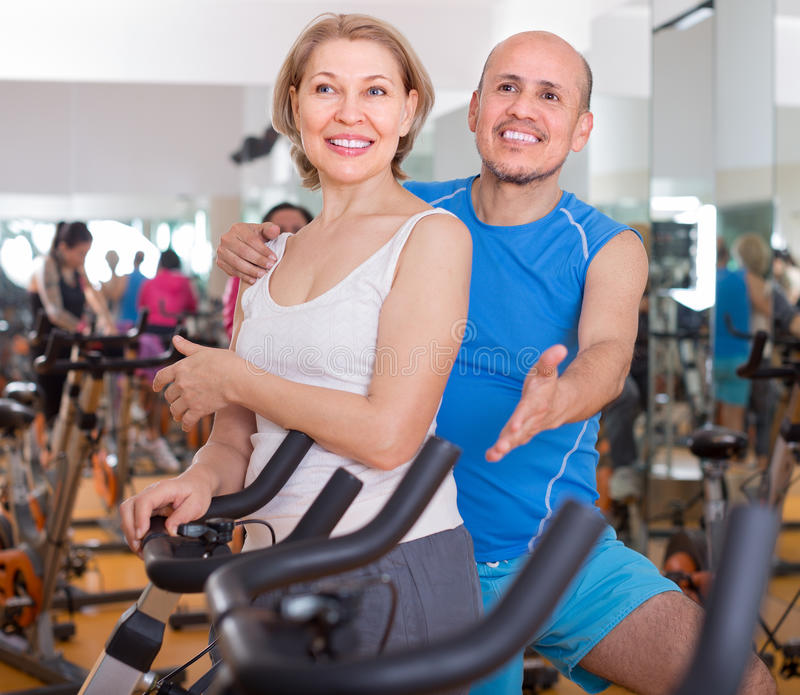 Mature couple posing in the gym. Smiling mature couple posing in the gym royalty free stock image