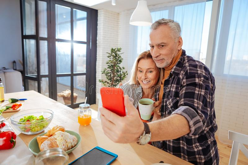 Mature couple posing for photo while sitting in the kitchen stock photography