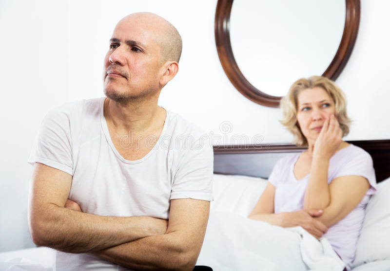 Mature couple quarrels in bed stock photo