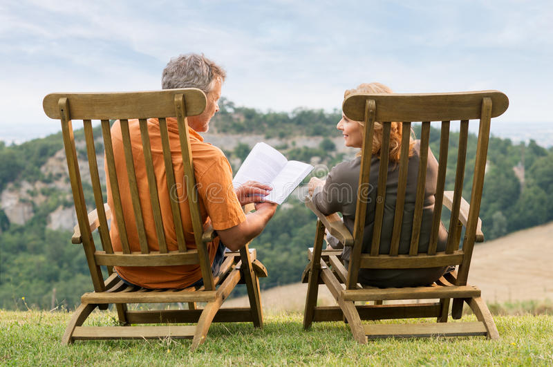 Mature Couple Reading Book. Rear View Of Mature Couple Sitting On Lounge Chair Reading Book