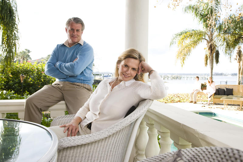 Mature couple relaxing on terrace. Portrait of mature couple relaxing on waterfront terrace stock photography