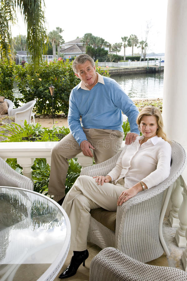 Mature couple relaxing on terrace. Portrait of mature couple relaxing on waterfront terrace royalty free stock photography