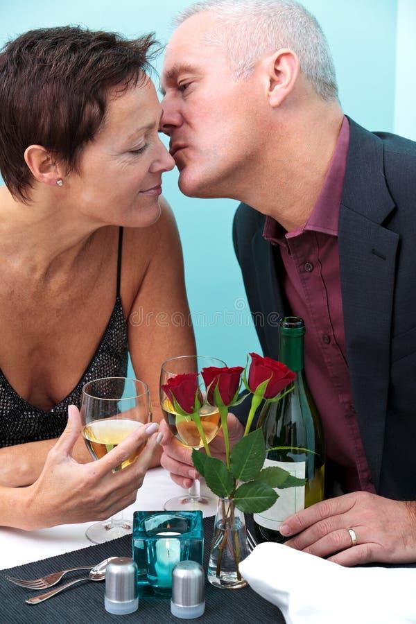 Mature couple restaurant kiss stock images