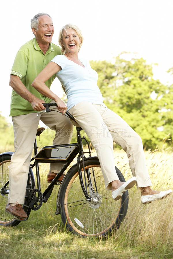 Mature couple riding bike in countryside stock photos