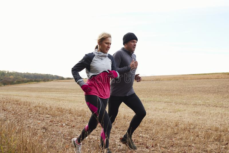 Mature Couple Running Around Autumn Field Together stock images