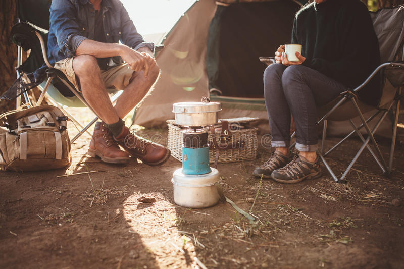 Mature couple sitting around a camp stove at campsite royalty free stock images