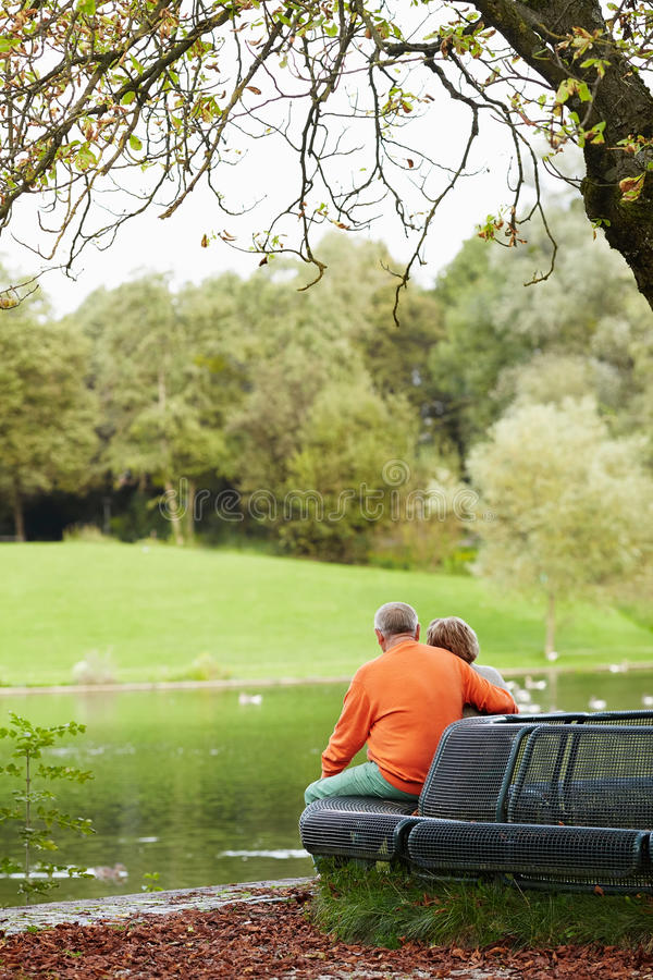 Mature couple sitting on bench in park stock photo