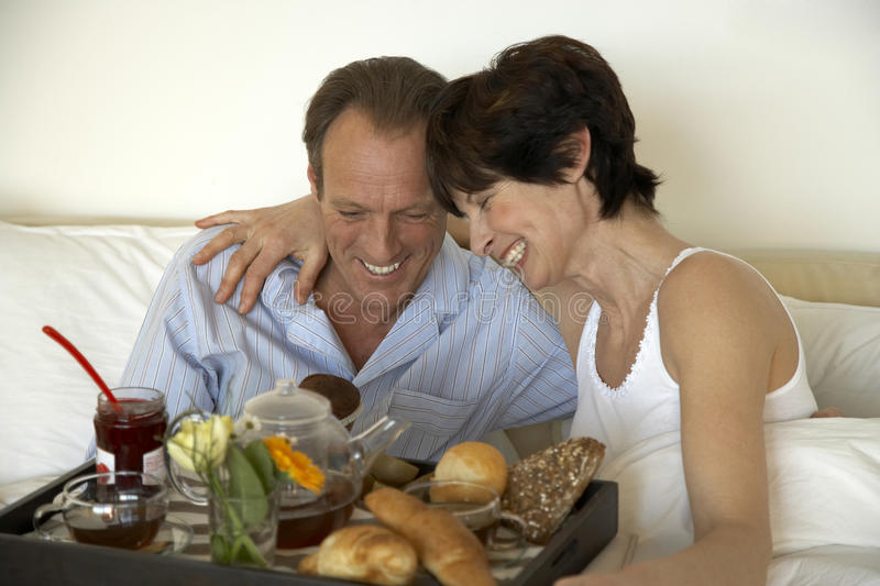 Mature couple sitting with breakfast and smiling royalty free stock images