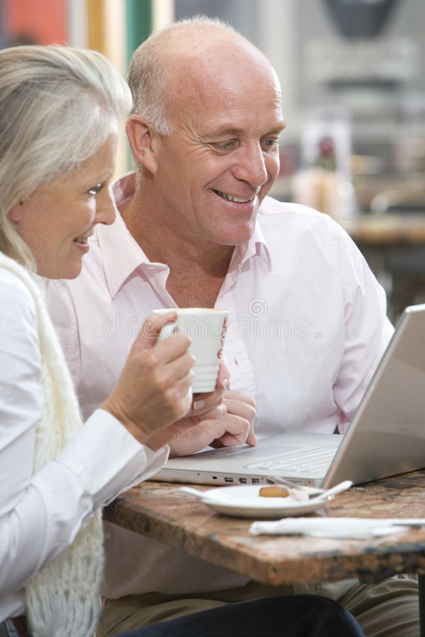 Mature couple sitting in cafe with coffees, looking at laptop, smiling royalty free stock image