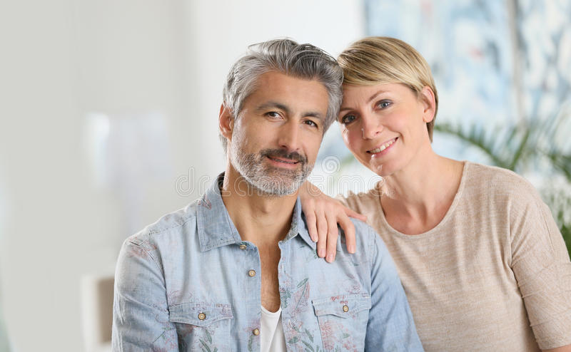 Mature couple sitting at home stock photo