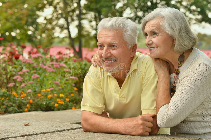 Mature couple in spring park. Happy mature couple in a spring park stock photo