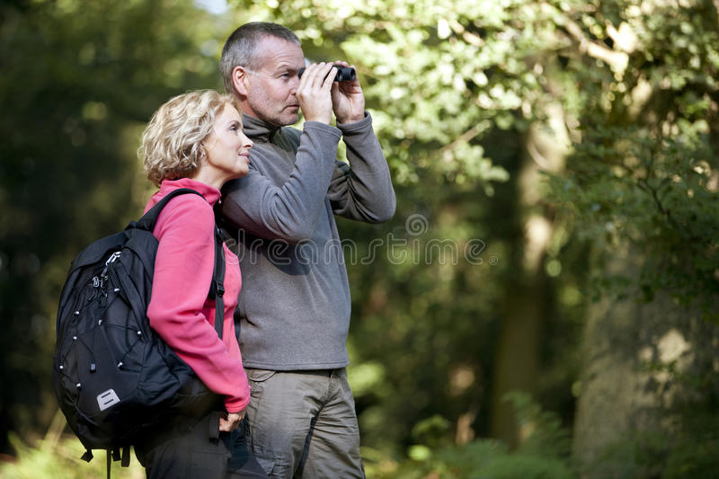 A mature couple standing in the countryside, man looking through binoculars royalty free stock photos