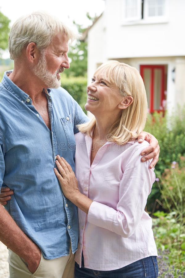 Mature Couple Standing In Garden In Front Of Dream Home In Countryside stock images