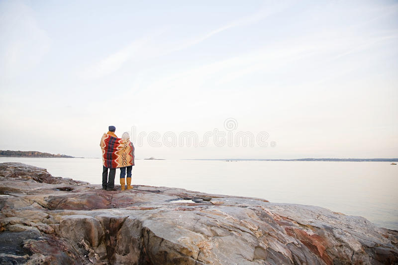 Mature couple standing on rocks together stock image