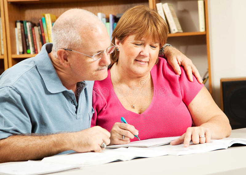 Mature Couple Studies in Library royalty free stock photography